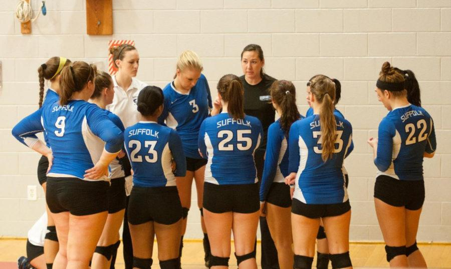 Coach Kristine Mickelson (black shirt) discusses her game plan with the team in her first year coaching in the 2013-14 season.