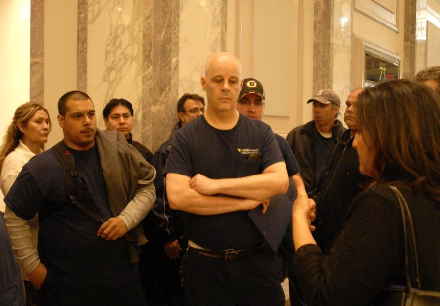 Roaxana Rivera (right corner) addresses facilities and maintenance workers in the lobby of 73 Tremont. 