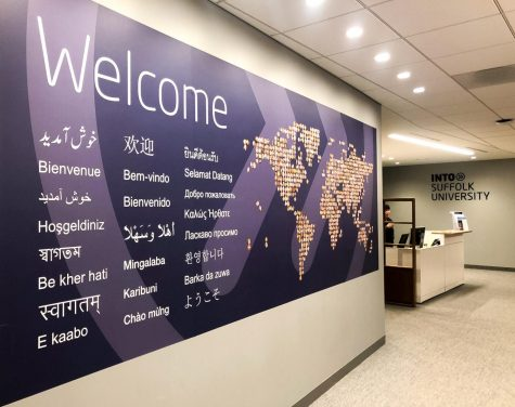 "A wall with ""welcome"" written on it in different languages at Into Suffolk University."