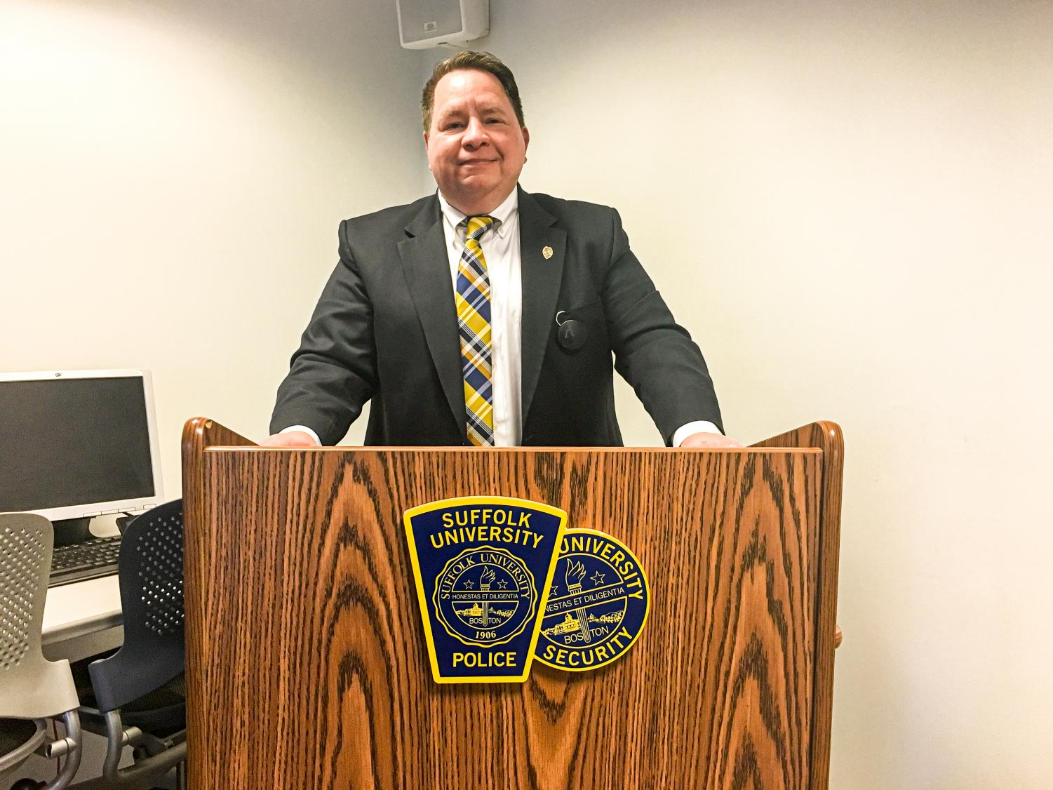 New interim Chief of Police Kenneth Walsh poses with the Suffolk University Police and Suffolk University Security seal