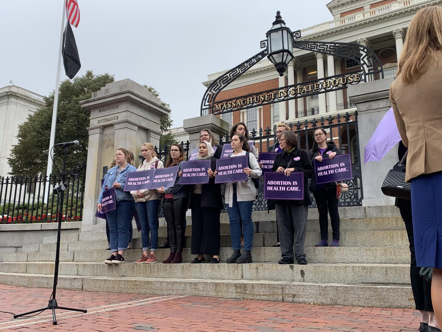Protestors stand in front of the Massachusetts State House Oct. 1
