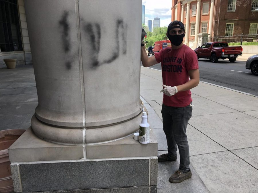 A Good Samaritan helps clean off graffiti from Sargent Hall. The building had been defaced during protests Sunday night.
