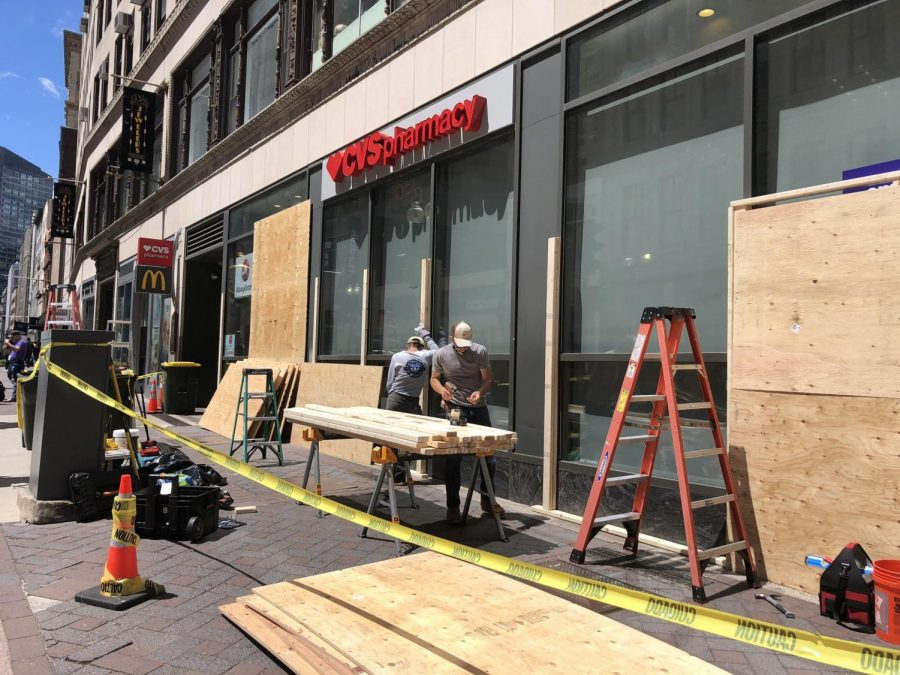 Workers put wooden boards over the windows of a CVS in Dowtown Crossing Monday morning.