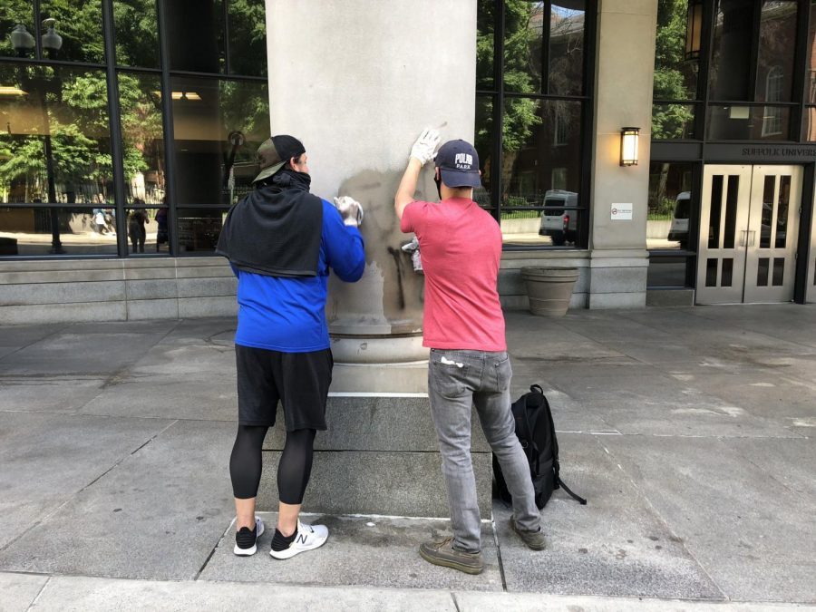 Good Samaritans clean off graffiti from the outside of Sargent Hall Monday morning, after protests broke in Boston Sunday night.