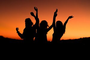 Three girls dance in front of a sunset.