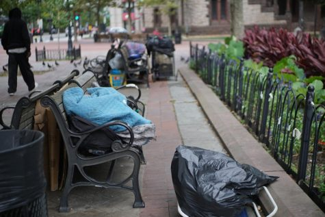 A person sleeps on a bench in Copley Square