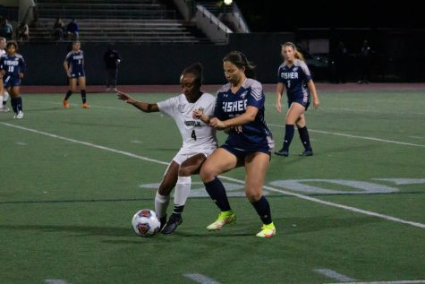 Freshman forward Jazmya Harris fights for possession with Fisher defender